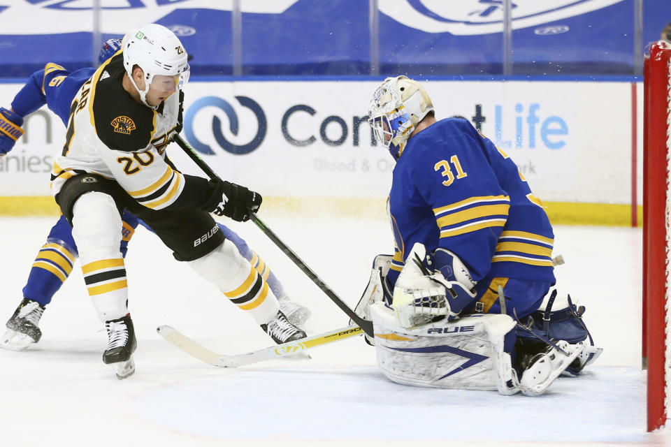 Buffalo Sabres goalie Dustin Tokarski (31) stops Boston Bruins forward Curtis Larzar (20) during the first period of an NHL hockey game, Thursday, April 22, 2021, in Buffalo, N.Y. (AP Photo/Jeffrey T. Barnes)