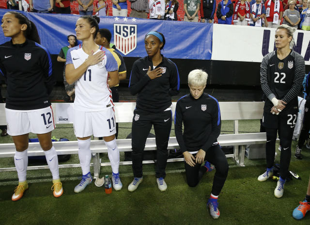 FILE - In this Sept. 18, 2016, file photo, United States' Megan Rapinoe, right, kneels next to teammates Christen Press (12), Ali Krieger (11), Crystal Dunn (16) and Ashlyn Harris (22) as the national anthem is played before the team's exhibition soccer match against the Netherlands in Atlanta. The U.S. women's national team wants the U.S. Soccer Federation to repeal the anthem policy it instituted after Rapinoe started kneeling during the national anthem. The U.S. women's team also wants the federation to state publicly that the policy was wrong and issue an apology to the team's black players and supporters. (AP Photo/John Bazemore, File)