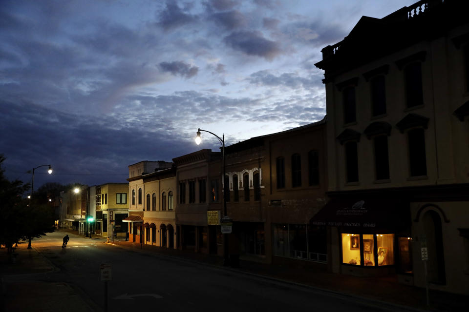 FILE- In this Oct. 28, 2017, file photo the storefront window of a portrait studio is lit up along a downtown street at dusk in Lumberton, N.C. Despite a decade-plus of economic growth, Americans have slowed the pace at which they're forming new companies, a trend that risks further widening the gap between the most affluent and everyone else. (AP Photo/David Goldman, File)