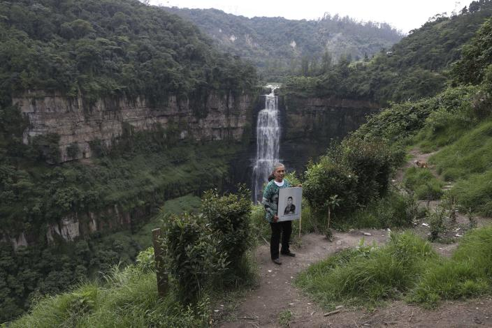 """Doris Tejada, the mother of Oscar Alexander Morales, holds a photo of her son who disappeared on New Year's eve 2007, as she poses for a portrait at the Tequendama Falls, in Soacha, Colombia, Thursday, April 8, 2021. Tejada and her husband found out that their son indeed is on the list of the """"false positives,"""" victims of extrajudicial executions by members of Colombia's army who were falsely presented as guerrillas killed in combat during the country's internal conflict, which ended with the 2016 demobilization of the Revolutionary Armed Forces of Colombia. (AP Photo/Fernando Vergara)"""