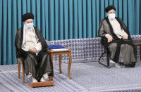 In this photo released by an official website of the office of the Iranian supreme leader, Supreme Leader Ayatollah Ali Khamenei, left, sits in an endorsement ceremony to give his official seal of approval to newly elected President Ebrahim Raisi, right, in Tehran, Iran, Tuesday, Aug. 3, 2021. (Office of the Iranian Supreme Leader via AP)