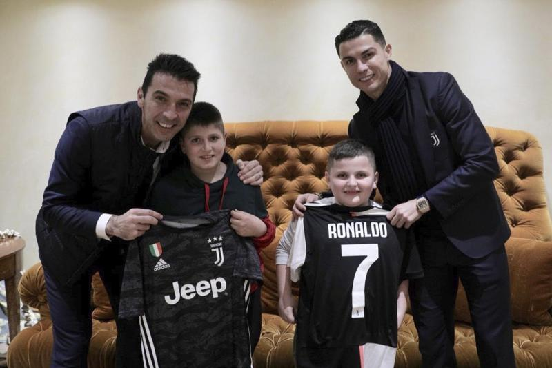 Juventus' players Cristiano Ronaldo, right, and Gianluigi Buffon, left, pose with Aurel Lala and Alesio Cakoni, in Rome on Friday, Dec. 6, 2019. The two Albanian children were injured when they escaped their collapsing flat jolted from the Nov. 26 6.4-magnitude earthquake, that killed 51 persons and injured more than 3,000 others. They lost each two family members but their dream came true when Prime Minister Edi Rama took them to Rome, Italy to meet with their sport idols Ronaldo and Buffon. (Albanian Prime Minster Office via AP)