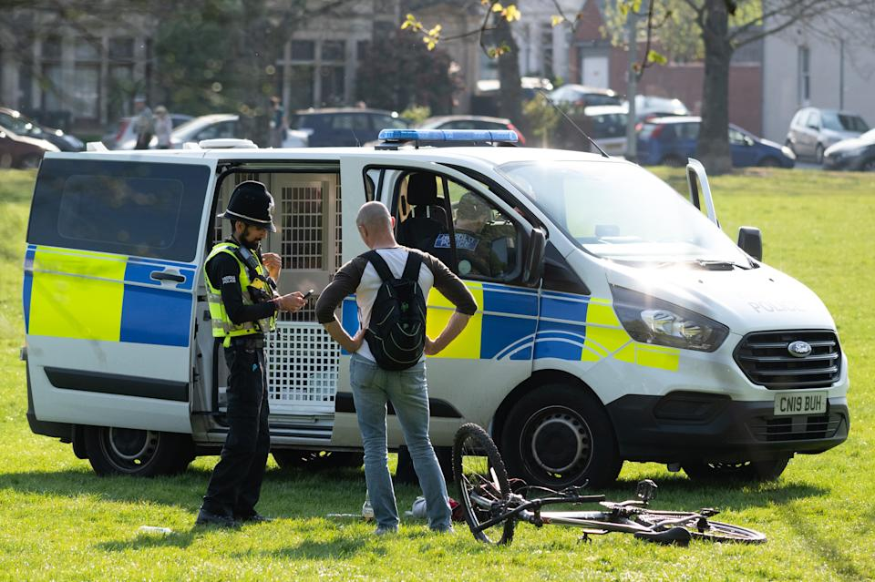 CARDIFF, UNITED KINGDOM - APRIL 11: A police officer speaks to a man on Roath Recreation Ground on April 11, 2020 in Cardiff, United Kingdom. Police have stepped up patrols to prevent people from travelling to beaches and beauty spots over the Easter weekend. The Coronavirus (COVID-19) pandemic has spread to many countries across the world, claiming over 100,000 lives and infecting over 1 million people. (Photo by Matthew Horwood/Getty Images)