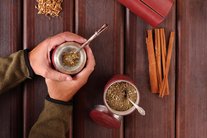 Man holding a yerba mate spice drunk in his hands.