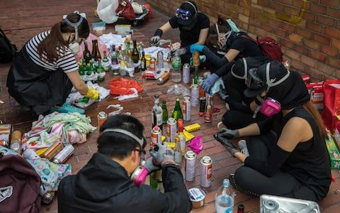 Protesters make molotov cocktails while camped out at the city's Polytechnic University  - Credit: AFP