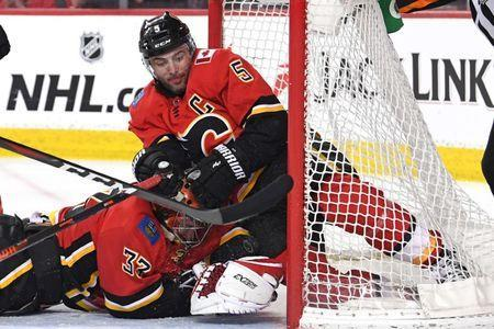 Mar 19, 2019; Calgary, Alberta, CAN; Calgary Flames defenseman Mark Giordano (5) and goalie David Rittich (33) makes a save against from the Columbus Blue Jackets in the second period at Scotiabank Saddledome. Mandatory Credit: Candice Ward-USA TODAY Sports