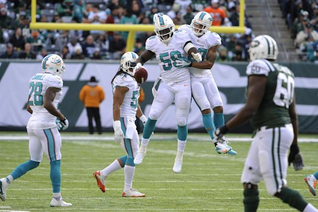 Miami Dolphins middle linebacker Dannell Ellerbe (59) celebrates with safety Jimmy Wilson (27) after intercepting a pass from New York Jets quarterback Geno Smith during the first half of an NFL football game on Sunday, Dec. 1, 2013, in East Rutherford, N.J. (AP Photo/Bill Kostroun)