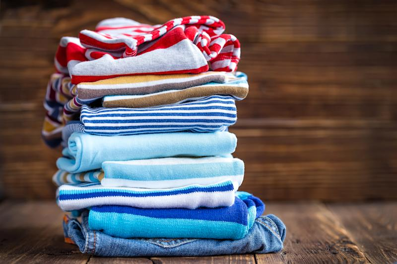 Stack of folded children's clothing on a wood floor.