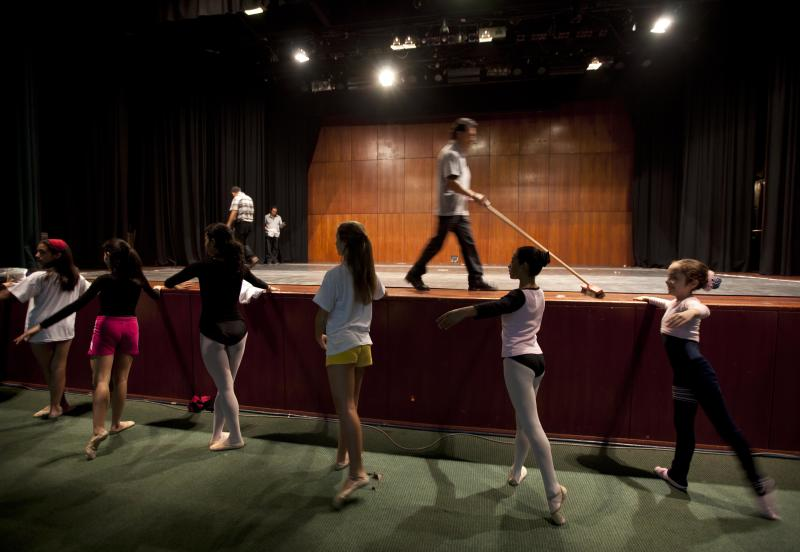 In this Sept. 3, 2012 photo, dancers practice for a competition between ballet schools as workers prepare the dance stage inside the National Museum in Lima, Peru. Nearly 100 girls and boys from Colombia, Venezuela, Chile, France and Peru are submitting themselves to a week-long competition hoping to win medals from Peru's national ballet school _ and perhaps a grant to study in Miami. (AP Photo/Martin Mejia)