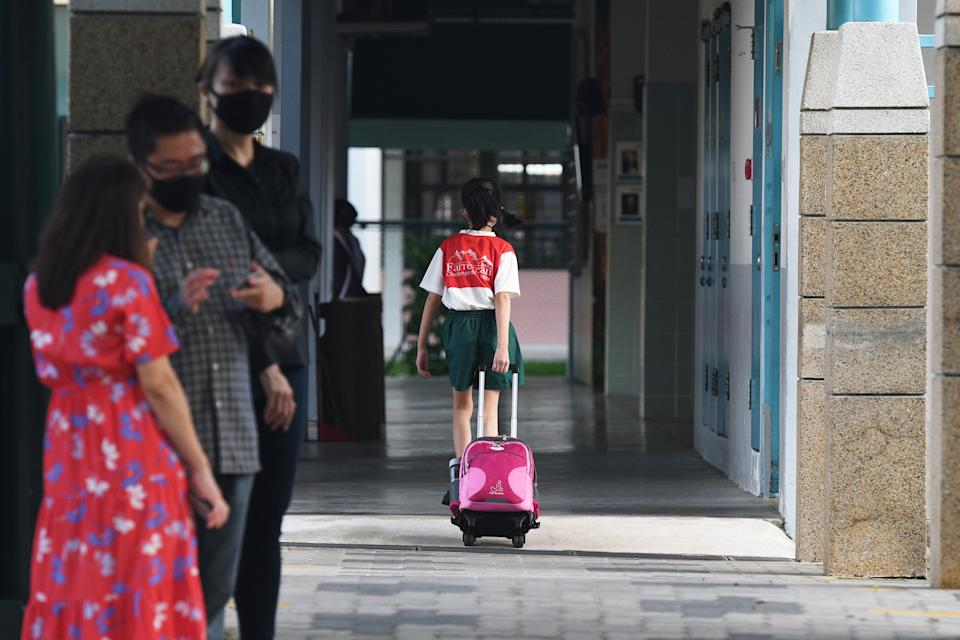 A primary school student pulling a school bag arrives at school in Singapore.