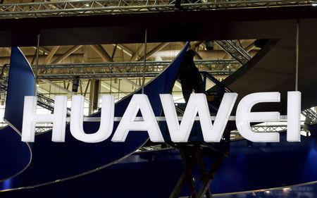 A worker adjusts the logo at the stand of Huawei at the CeBIT trade fair in Hanover, in this file picture taken March 15, 2015.  REUTERS/Morris Mac Matzen/File Photo
