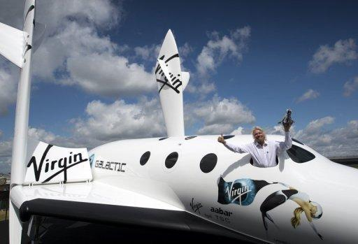 British billionaire Richard Branson in the window of a replica of the spaceship he plans to launch for his new Virgin Galactic space tourism programme, at the Farnborough Air Show in Britain. Branson said Wednesday that he and his family will be the first on board his new Virgin Galactic space tourism programme