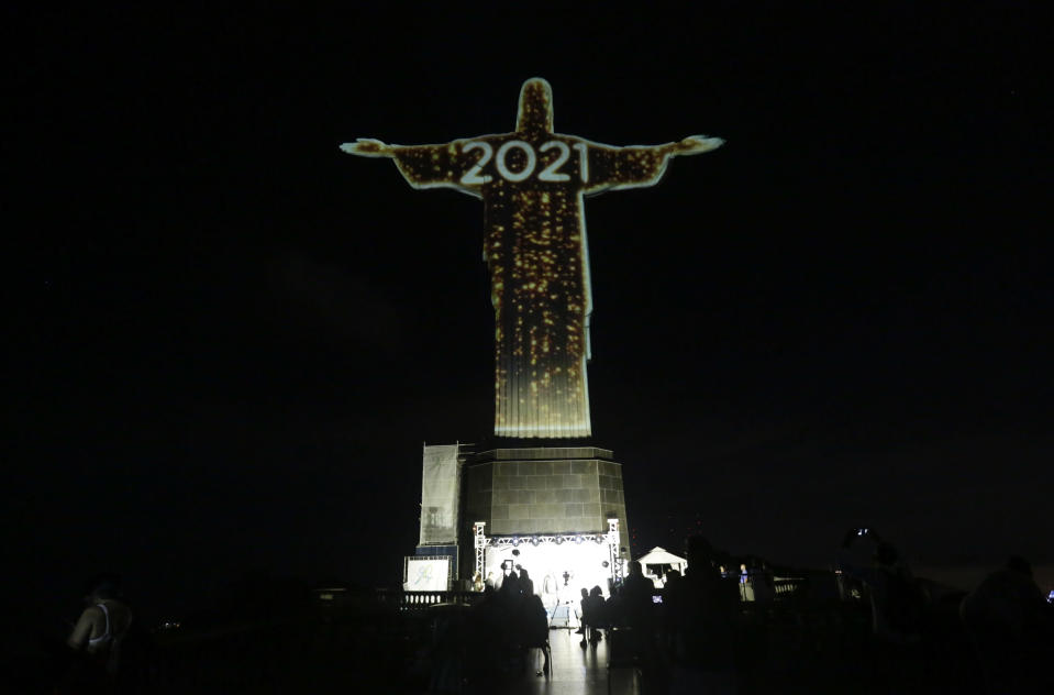 The iconic Christ the Redeemer statue is lit up during a New Year's Eve celebration in Rio de Janeiro, Brazil, Thursday, Dec. 31, 2020. (AP Photo/Bruna Prado)