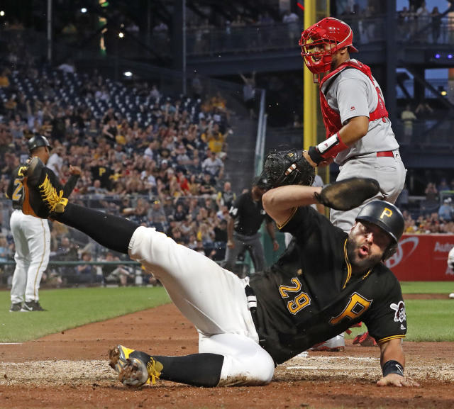 Pittsburgh Pirates' Francisco Cervelli (29) scores past St. Louis Cardinals catcher Francisco Pena on a triple by Corey Dickerson in the sixth inning of a baseball game in Pittsburgh, Friday, May 25, 2018. (AP Photo/Gene J. Puskar)