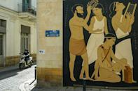 A mural by Fikos located near the Green Line that divides Nicosia shows King Onassagoras, who ruled the kingdom of Ledra around 672 BC, next to three female figures -- one of them Nicosia, depicted as a woman split in half