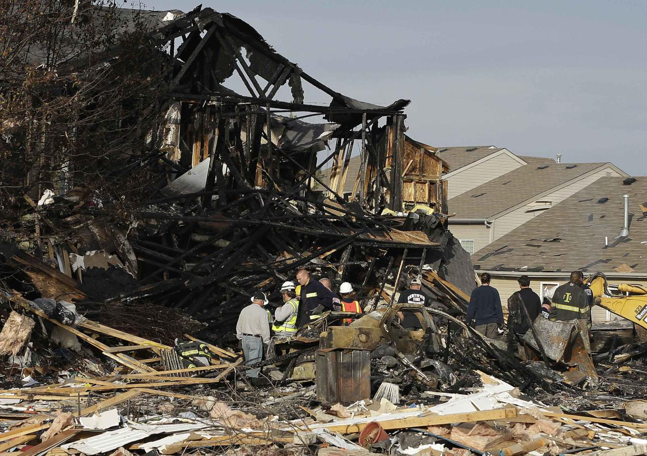 Emergency personnel work at the site of a home that was destroyed by an explosion Sunday, Nov. 11, 2012, in Indianapolis. Nearly three dozen homes were damaged or destroyed, and seven people were taken to a hospital with injuries, authorities said Sunday. The powerful nighttime blast shattered windows, crumpled walls and could be felt at least three miles away. (AP Photo/Darron Cummings)