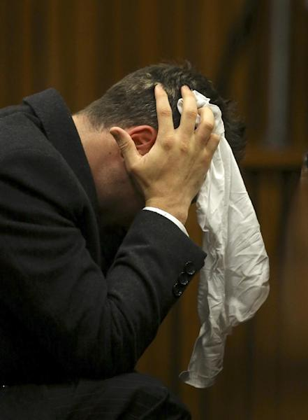 Oscar Pistorius covers his head with a handkerchief after he had reached for a bucket at his feet while listening to cross questioning about the events surrounding the shooting death of his girlfriend Reeva Steenkamp, in his second week in court during his trial in Pretoria, South Africa, Monday, March 10, 2014. Pistorius is charged with the shooting death of his girlfriend Steenkamp, on Valentines Day in 2013. (AP Photo/Siphiwe Sibeko, Pool)
