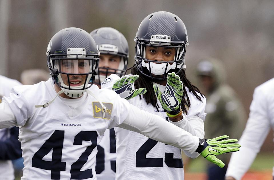 Seattle Seahawks' Chris Maragos (42) and Richard Sherman run through a drill at an NFL football practice Thursday, Jan. 16, 2014, in Renton, Wash. The Seahawks are to play the San Francisco 49ers on Sunday in the NFC championship game. (AP Photo/Elaine Thompson)