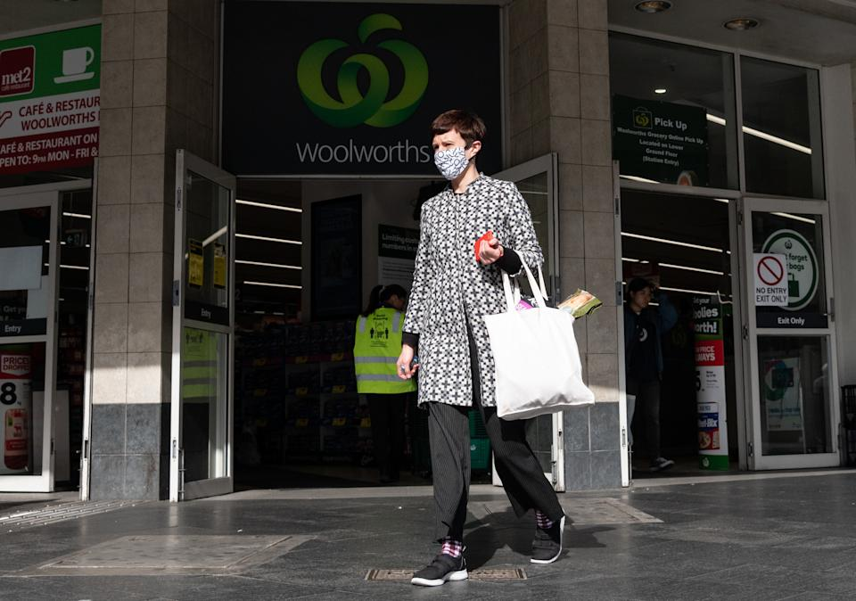 A shopper wearing a face mask leaving a Woolworths shop in Sydney.