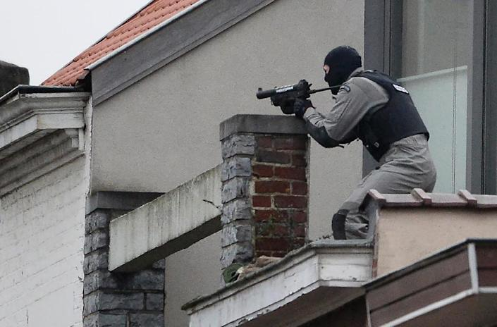 A member of the special forces takes position on a roof near the site of a shooting in the southern Forest district of Brussels, on March 15, 2016 (AFP Photo/Dirk Waem)