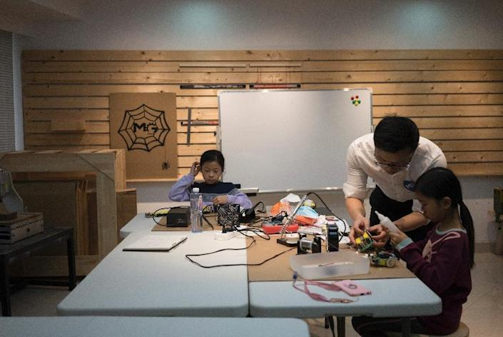 A teacher instructs children at 'MG Space', a small-scale workshop in Shenzhen, southern China (AFP Photo/FRED DUFOUR)