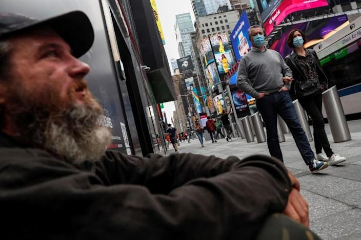 People wearing protective face mask look at Eric Gourley as he sits on the sidewalk outside a closed store at Times Square in New York City