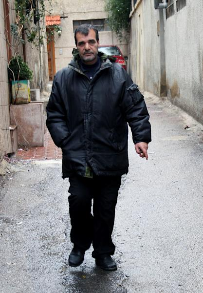 This Saturday, Dec. 7, 2013 photo shows Ahmed Luay, whose son Hassan was killed just over a month ago while fighting in the Syrian army against rebels, walking in Damascus, Syria. Like many government supporters, Luay contends that Syria's nearly 3-year civil war boils down to a fight against foreign jihadis trying to impose Shariah rule, dismissing the opposition view that they are fighting for reforms. (AP Photo)