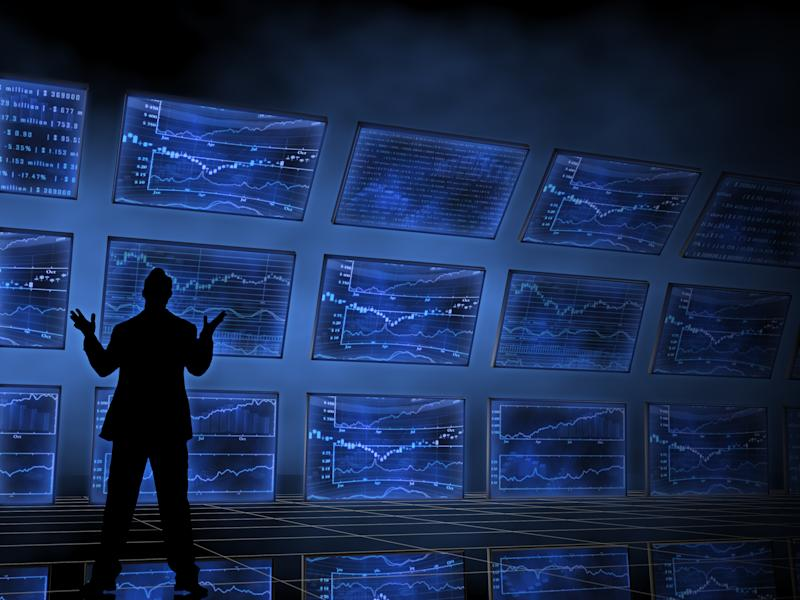Silhouette of person standing in front of multiple screens displaying charts
