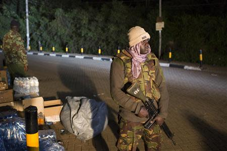 Police officers guard the edge of a security perimeter put into place a distance from the Westgate Shopping Centre in Nairobi, during a standoff operation between security forces and gunmen