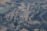 In this aerial photo taken from a helicopter, structures destroyed by a wildfire are seen in Lytton, British Columbia, on Thursday, July 1, 2021. A wildfire that forced people to flee a small town in British Columbia that had set record high temperatures for Canada on three consecutive days burned out of control Thursday as relatives desperately sought information on evacuees. (Darryl Dyck/The Canadian Press via AP)