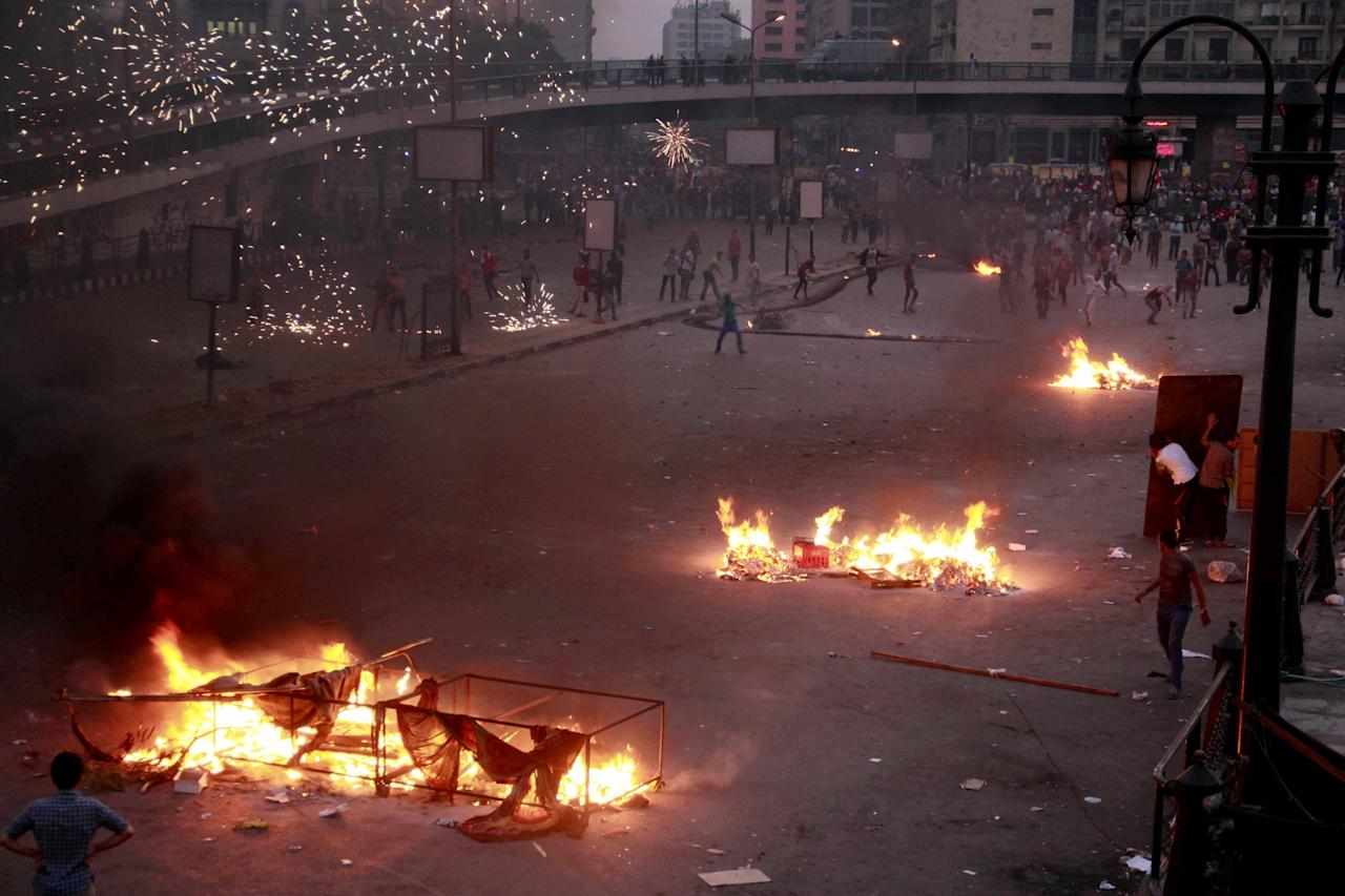 Pro-military crowds and supporters of the former president, Mohammed Morsi, pelt each other with rocks, fireworks and firebombs in street battles near Ramsis Square, Cairo, Egypt, Sunday, Oct. 6, 2013. The deadly clashes took place on the 40th anniversary of the start of the 1973 Mideast war, a holiday the military-backed government had wanted to use to pay tribute to the armed forces, whose chief ousted Morsi in a popularly supported coup on July 3. (AP Photo/Emad Abdul Rahman)