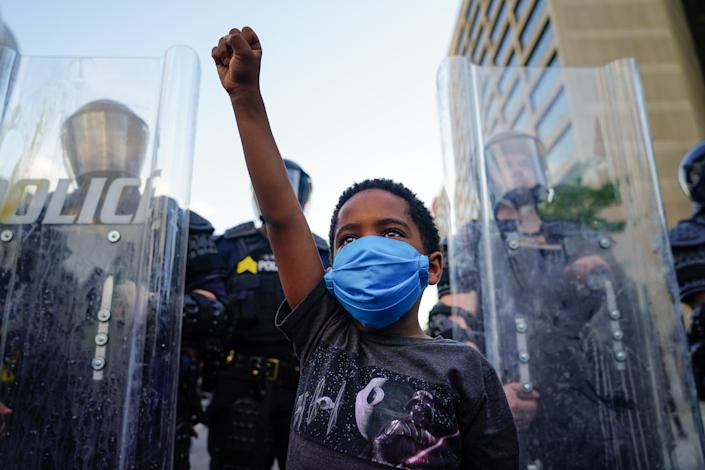 A young boy raises his fist for a photo by a family friend during a demonstration over the Minneapolis death of George Floyd while in police custody on May 31, 2020 in Atlanta, Georgia. (Photo by Elijah Nouvelage/Getty Images)
