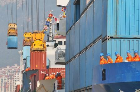 Workers look at cranes lifting containers onto cargo vessels at a port in Yantai, Shandong
