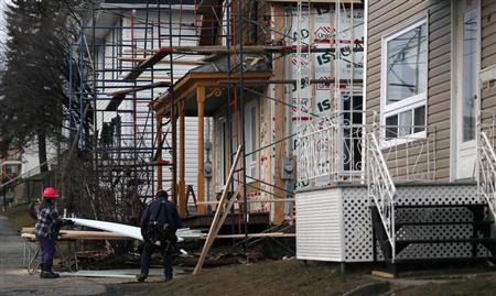 Construction workers work on a house in Lac-Megantic