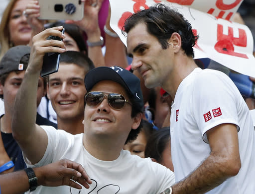 Roger Federer, of Switzerland, poses with a fan after defeating Nick Kyrgios, of Australia, during the third round of the U.S. Open tennis tournament, Saturday, Sept. 1, 2018, in New York. (AP Photo/Jason DeCrow)
