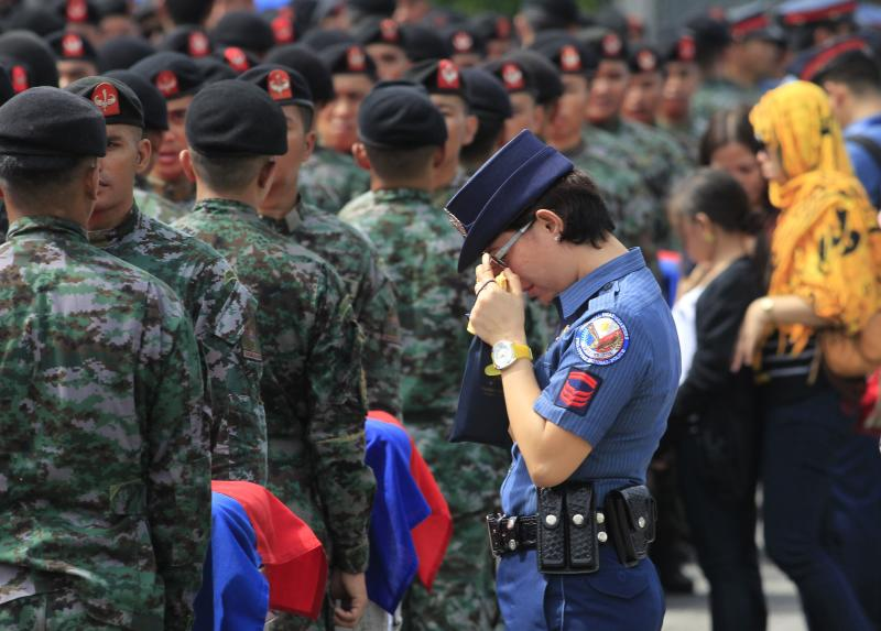 A policewoman wipes her tears as she stands in front of metal caskets containing the bodies of police who were killed in Sunday's clash with Muslim rebels, at Villamor Air Base in Pasay city
