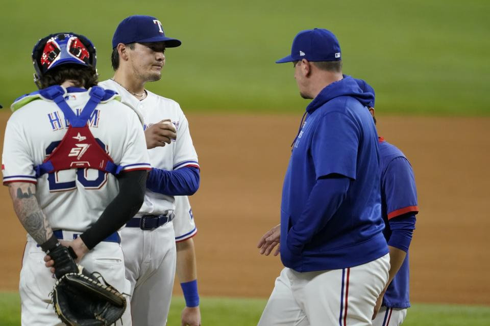 Texas Rangers catcher Jonah Heim (28) stands by as starting pitcher Kohei Arihara, second from left, gets a visit from pitching coach Doug Mathis, right, in the fifth inning of a baseball game against the Houston Astros in Arlington, Texas, Wednesday, Sept. 15, 2021. (AP Photo/Tony Gutierrez)