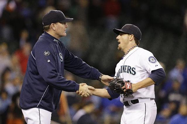 Seattle Mariners manager Eric Wedge, left, shakes hands with closing pitcher Danny Farquhar after the team beat the Kansas City Royals in a baseball game Tuesday, Sept. 24, 2013, in Seattle. The Mariner won 4-0. (AP Photo/Elaine Thompson)