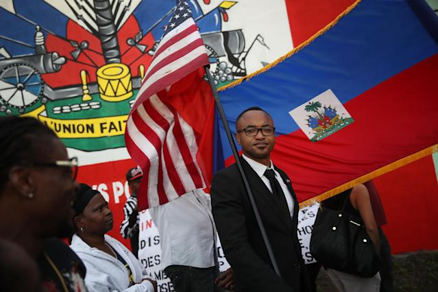 <p>Fandzy Bernadin holds an American flag as he joins with others to mark the 8th anniversary of the massive earthquake in Haiti and to condemn President Donald Trump's reported statement about immigrants from Haiti, Africa and El Salvador on Jan. 12, 2018 in Miami, Fla. (Photo: Joe Raedle/Getty Images) </p>