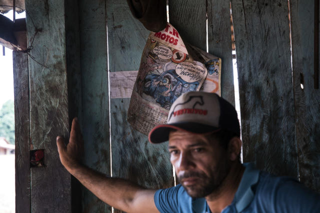 In this Sept. 2, 2019 photo, a customer stands next to a calendar featuring a comic that pokes fun at indigenous people in a mechanic shop along the road between the city of Paragominas and the village Ka 'a kyr, in Para state, Brazil. (AP Photo/Rodrigo Abd)