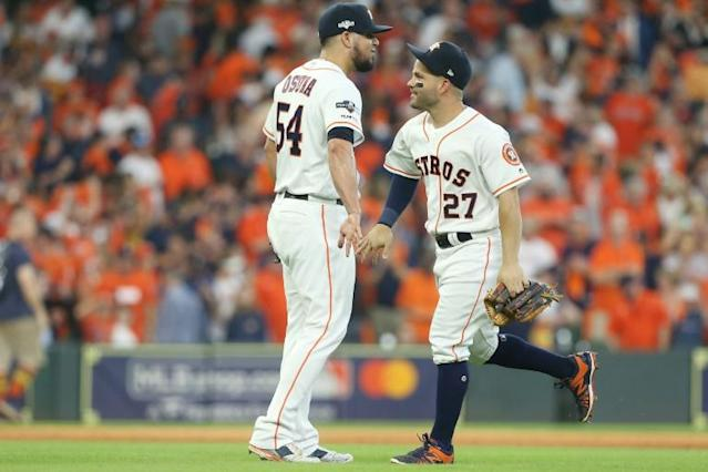 Houston's Roberto Osuna and Jose Altuve celebrate after the Astros' 6-2 victory over the Tampa Bay Rays in game one of their American League Division Series (AFP Photo/Bob Levey)