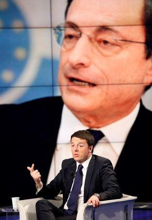 "Italy's Prime Minister Renzi gestures as a picture of Draghi, President of the ECB, is seen on a large screen behind him during television talk show ""Porta a Porta"" in Rome"