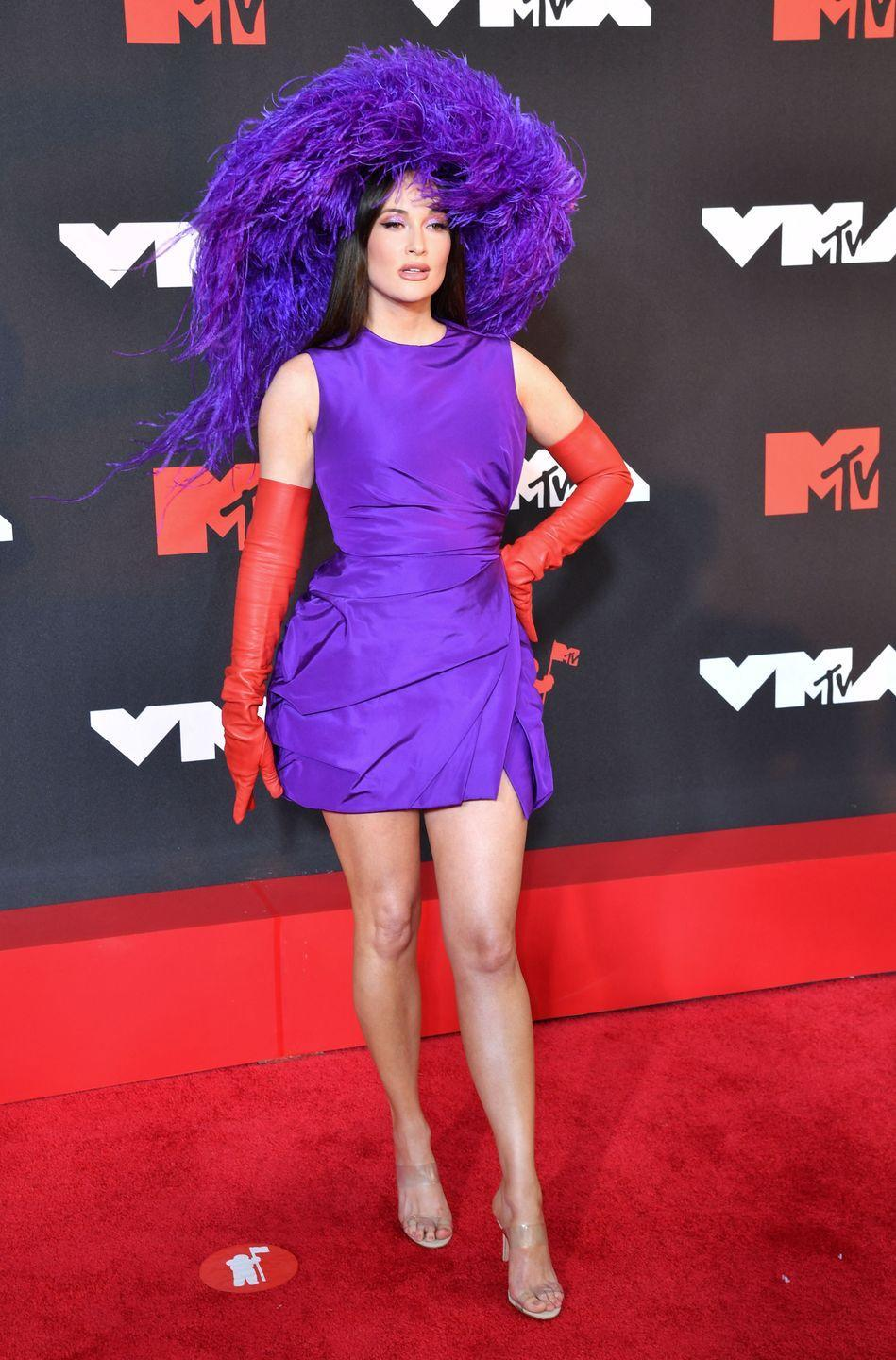 """<p>Kacey Musgraves went all-purple in a ruched mini dress and feathered headdress reminiscent of Lady Gaga's campy New York <a href=""""https://www.harpersbazaar.com/celebrity/latest/a37198084/lady-gaga-statement-purple-poncho-valentino-nyc/"""" rel=""""nofollow noopener"""" target=""""_blank"""" data-ylk=""""slk:street style moment"""" class=""""link rapid-noclick-resp"""">street style moment</a>. </p>"""