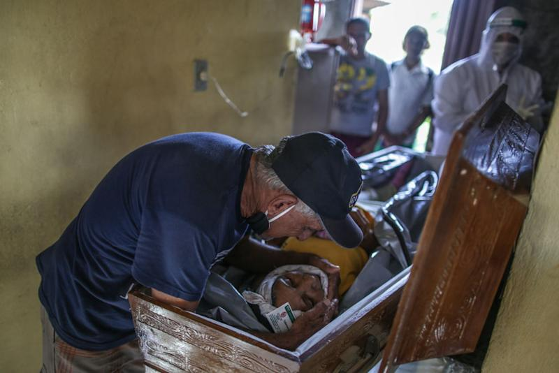Raimundo dos Santos cries and holds the body of his wife, Lucia Rodrigues dos Santos.