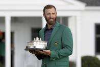 Dustin Johnson holds the trophy after being presented with his first green jacket after winning the Masters golf tournament Sunday, Nov. 15, 2020, in Augusta, Ga. (Curtis Compton/Atlanta Journal-Constitution via AP)