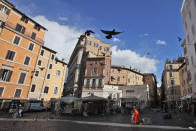Pigeons fly over Rome's Campo dei Fiori Square, Monday, March 15, 2021. Half of Italy's regions have gone into the strictest form of lockdown in a bid to curb the latest spike in coronavirus infections that have brought COVID-19 hospital admissions beyond manageable thresholds. (AP Photo/Alessandra Tarantino)