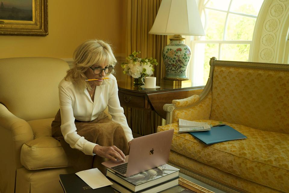 Another photograph captured her in action with a pencil between her teeth, her reading glasses on and typing on her Apple laptoop in  the Executive Residence's East Sitting Hall (Annie Leibovitz/Vogue)