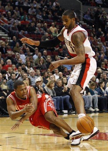 Houston Rockets' Kyle Lowry, left, loses the ball as Portland Trail Blazers' LaMarcus Aldridge (12) defends in the first quarter during an NBA basketball game on Wednesday, Feb. 8, 2012, in Portland, Ore. (AP Photo/Rick Bowmer)