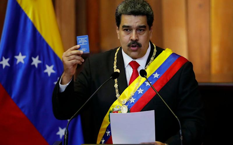 Venezuela's President Nicolas Maduro holds up a small copy of the constitution as he speaks during his swearing-in ceremony at the Supreme Court in Caracas - AP