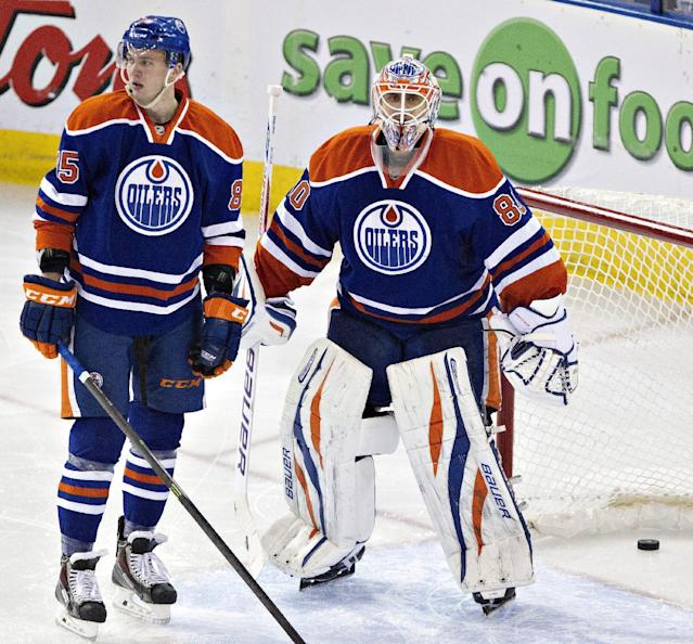 Edmonton Oilers' Martin Marincin (85) and goalie Ilya Bryzgalov (80) stand in front of the net after the Phoenix Coyotes scored a goal during the second period of an NHL hockey game Friday, Jan. 24, 2014, in Edmonton, Alberta. (AP Photo/The Canadian Press, Jason Franson)